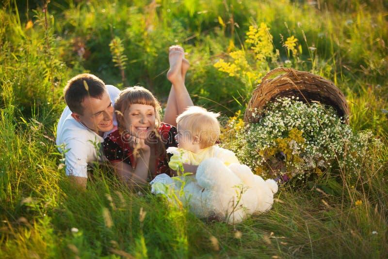 Famiglia felice divertendosi all'aperto nel prato di estate immagine stock libera da diritti