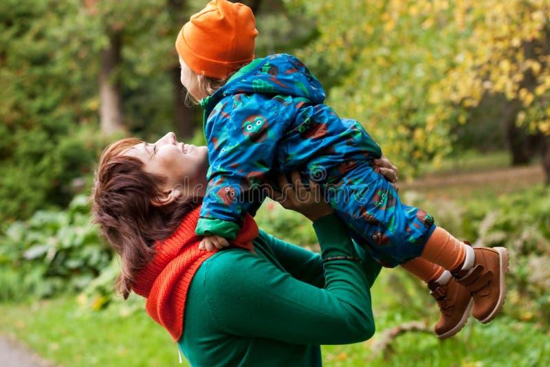 Famiglia felice divertendosi nel parco di autunno immagine stock
