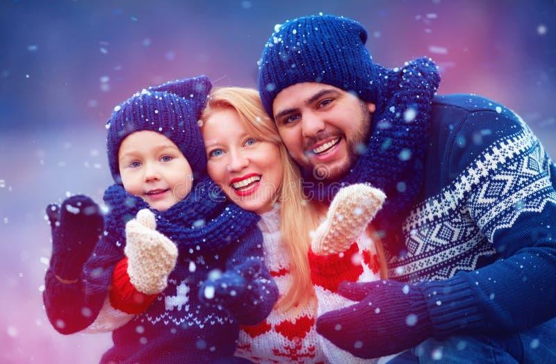 Famiglia felice divertendosi sotto la neve durante le vacanze invernali fotografia stock
