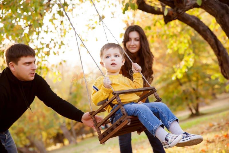 Famiglia felice divertendosi su un giro dell'oscillazione ad un giardino un il giorno di autunno immagini stock