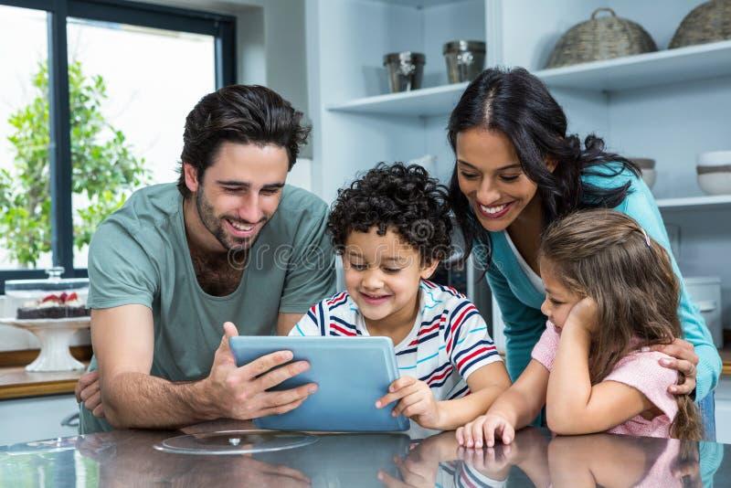 Famiglia felice facendo uso della compressa in cucina immagine stock libera da diritti
