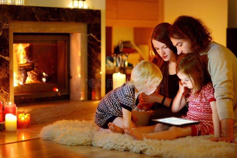 Famiglia felice facendo uso di un pc della compressa da un camino fotografia stock