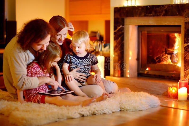Famiglia felice facendo uso di un pc della compressa da un camino immagini stock
