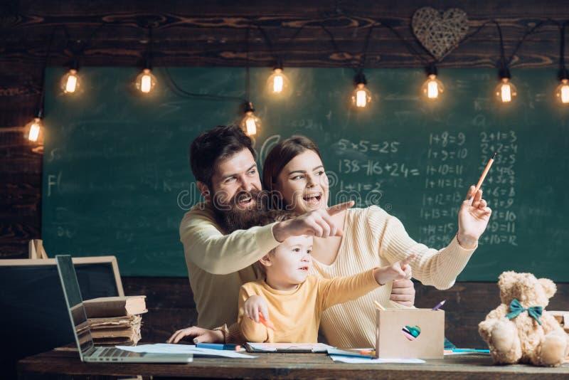 Famiglia felice La famiglia felice ha ottenuto l'idea luminosa Dita felici di sorriso e del punto della famiglia nella classe Fam fotografie stock libere da diritti