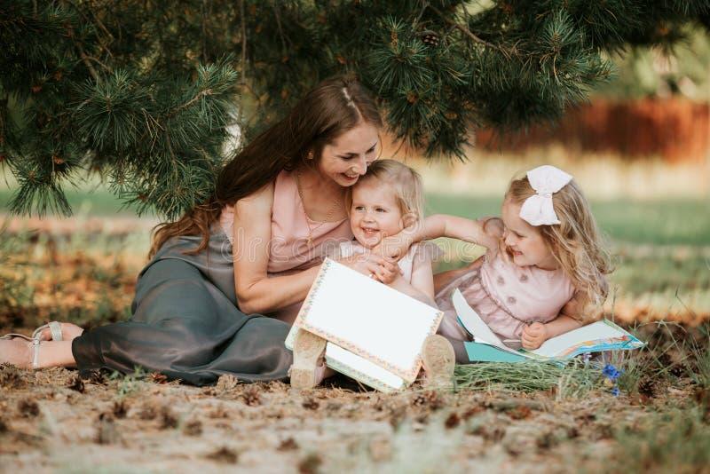 Famiglia felice - la mamma e due figlie stanno sedendo in un prato e stanno leggendo un libro Picnic immagine stock