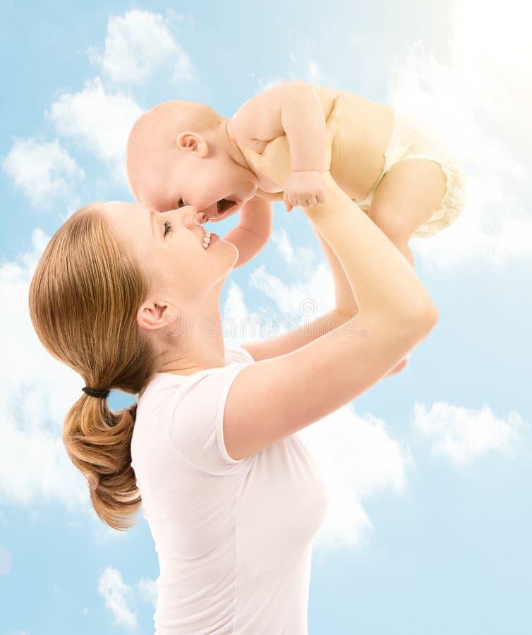 Famiglia felice. Madre che bacia bambino nel cielo immagine stock libera da diritti