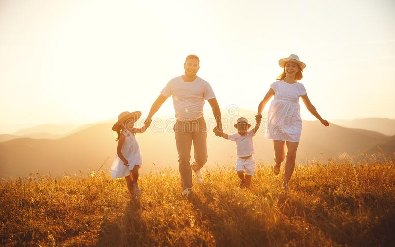 Famiglia felice: madre, padre, bambini figlio e figlia su sunse immagini stock