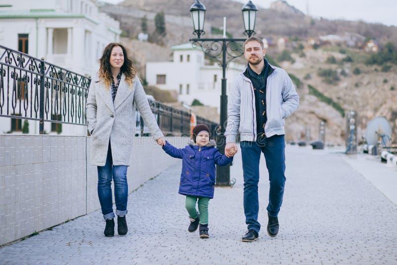 Famiglia felice - madre, padre e piccolo figlio camminanti nel porto fotografia stock