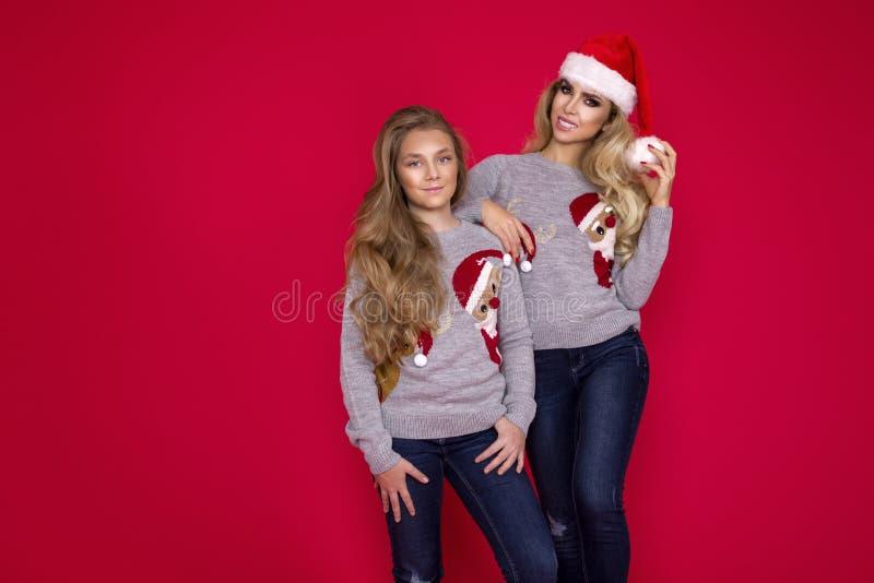 Famiglia felice in maglione di Natale che posa su un fondo rosso nello studio Godere degli abbracci di amore, la gente di feste M fotografie stock