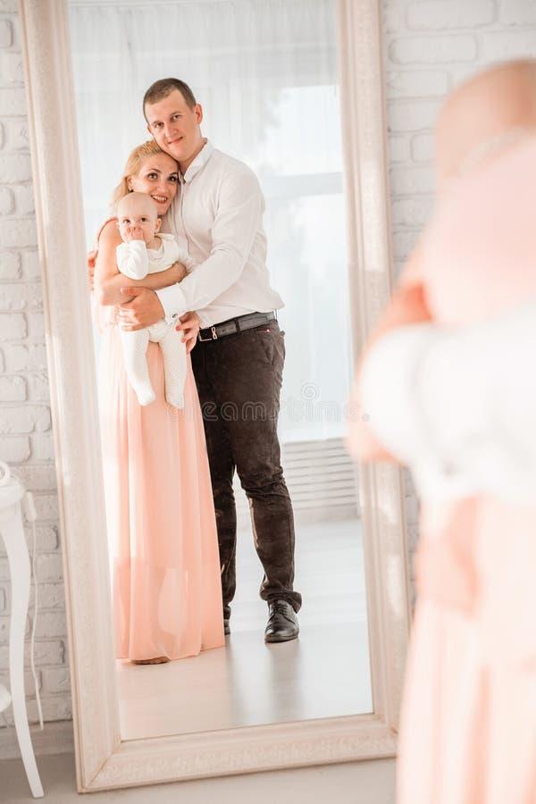 Famiglia felice - mamma, papà e figlio vicino allo specchio fotografia stock