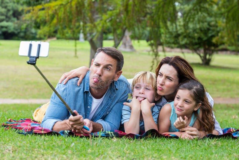 Famiglia felice nel parco che prende selfie fotografia stock
