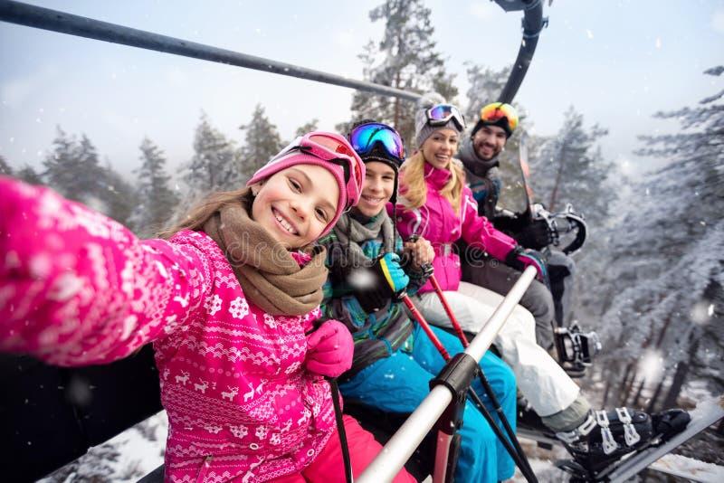 Famiglia felice nella salita della cabina di funivia da sciare terreno immagini stock