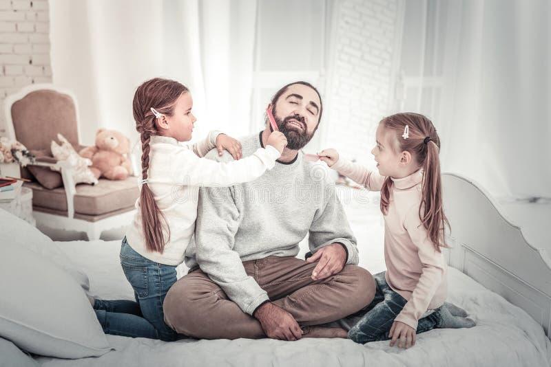 Famiglia felice Papà e due sorelle che giocano sul letto immagine stock libera da diritti