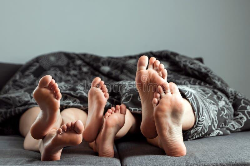 Famiglia felice, primo piano delle gambe che attaccano fuori da sotto la coperta Copi lo spazio Il concetto della famiglia, relaz fotografia stock