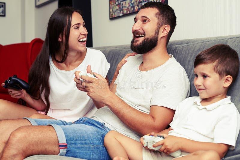 Famiglia felice rapita nel gioco del videogioco a casa immagini stock