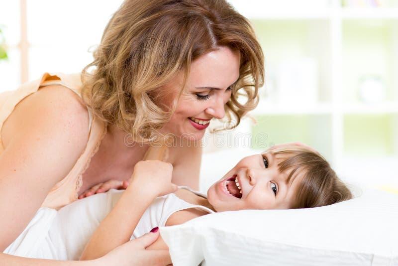 Famiglia felice - scherzi con il gioco della madre, risata e immagine stock