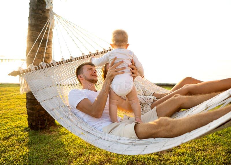 Famiglia felice su un'isola tropicale alla bugia di tramonto in un'amaca e giocare con il loro figlio immagine stock libera da diritti