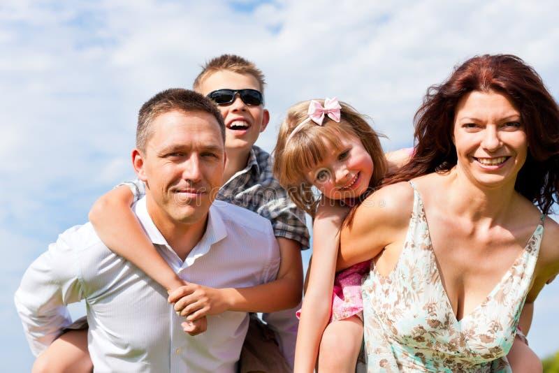 Famiglia felice su un prato in estate fotografia stock libera da diritti