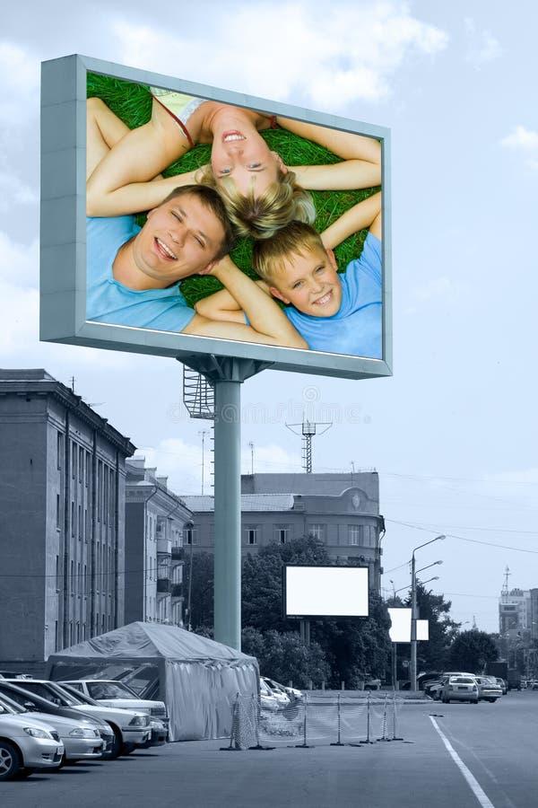 Famiglia felice sul tabellone per le affissioni esterno fotografia stock