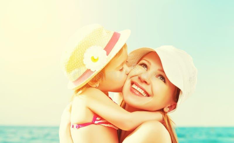 Famiglia felice sulla spiaggia figlia del bambino che bacia madre fotografia stock