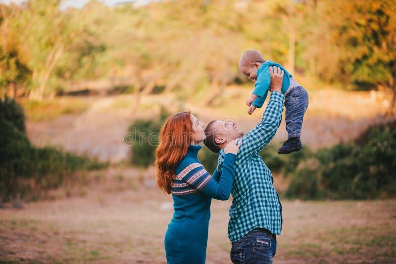 Famiglia felice in vestiti alla moda blu che cammina nella foresta di autunno immagine stock libera da diritti