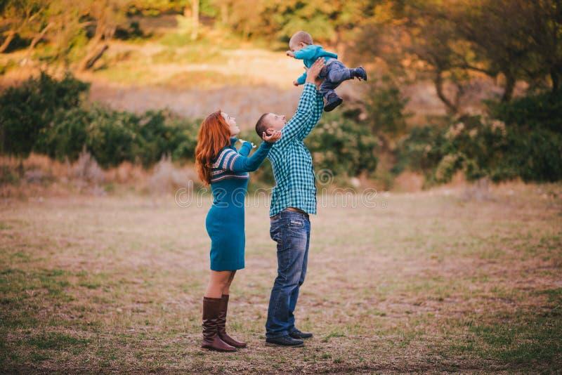 Famiglia felice in vestiti alla moda blu che cammina nella foresta di autunno immagini stock libere da diritti