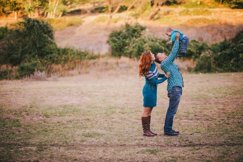 Famiglia felice in vestiti alla moda blu che cammina nella foresta di autunno immagine stock