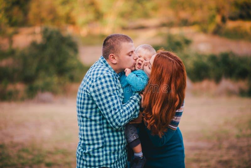 Famiglia felice in vestiti alla moda blu che cammina nella foresta di autunno fotografia stock