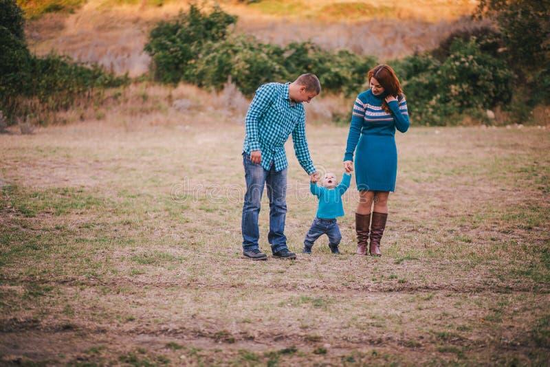 Famiglia felice in vestiti alla moda blu che cammina nella foresta di autunno immagini stock
