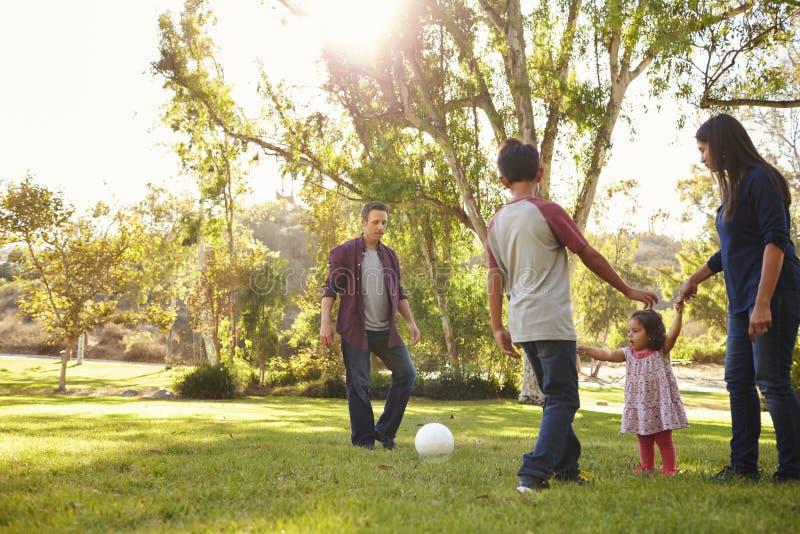 Famiglia giovane della corsa mista che gioca con la palla in un parco, backlit immagini stock