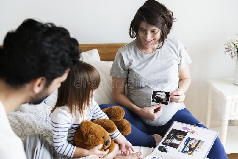 Famiglia incinta che guarda attraverso un album di foto della famiglia immagine stock libera da diritti