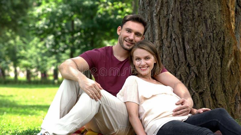 Famiglia incinta felice che si siede sotto l'albero in parco, corsi per i genitori futuri immagine stock libera da diritti