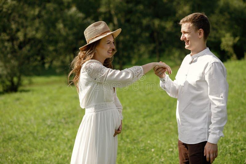 Famiglia incinta felice divertendosi tempo in natura di estate fotografia stock