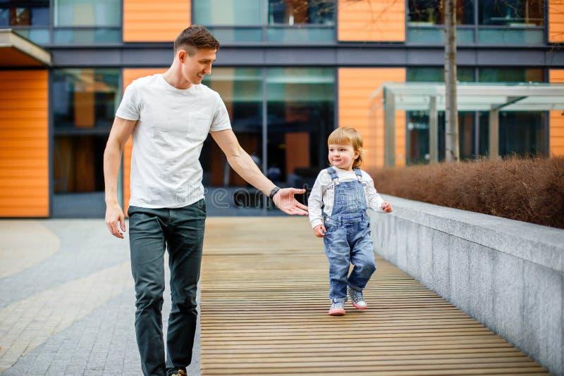 Famiglia, infanzia, paternità, svago e concetto della gente - il giovane padre felice e la piccola figlia passeggiano tramite le  immagine stock