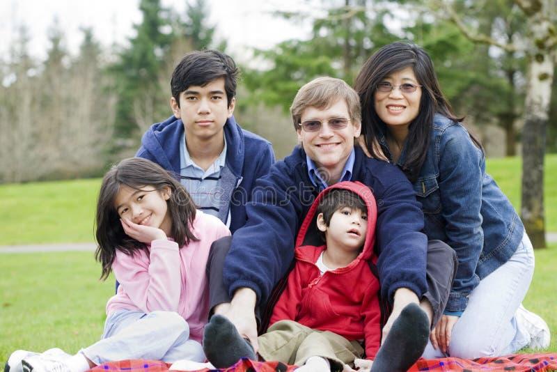Famiglia interrazziale felice che gode del giorno alla sosta fotografia stock
