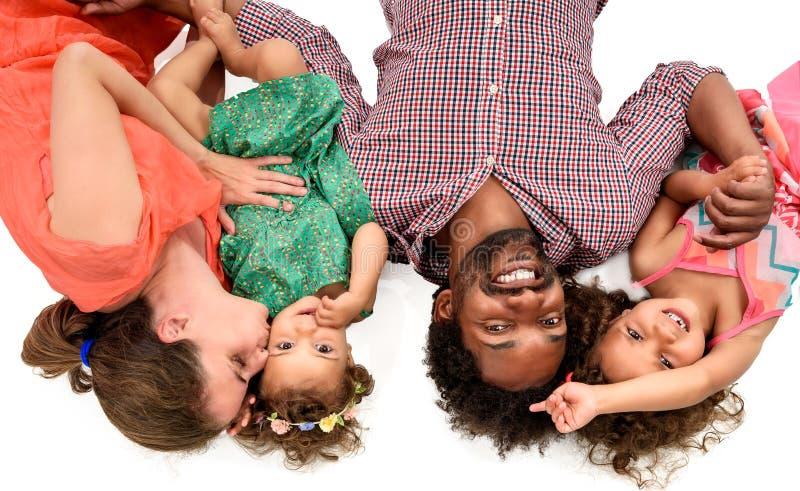 Famiglia interrazziale felice isolata su bianco immagine stock