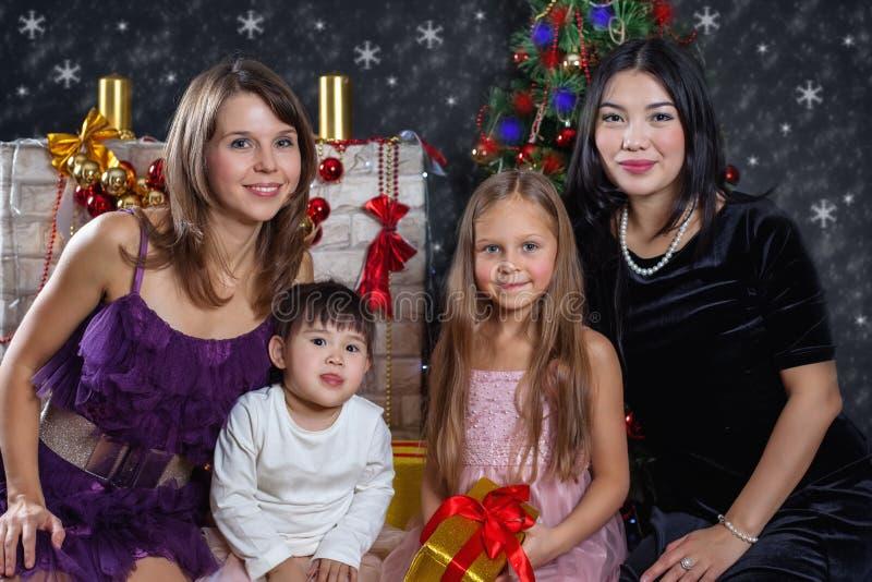 Famiglia interrazziale lesbica nei precedenti del Natale fotografie stock