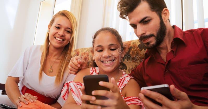 Famiglia ispana che ride giocando gioco sul telefono di Smartphone immagini stock