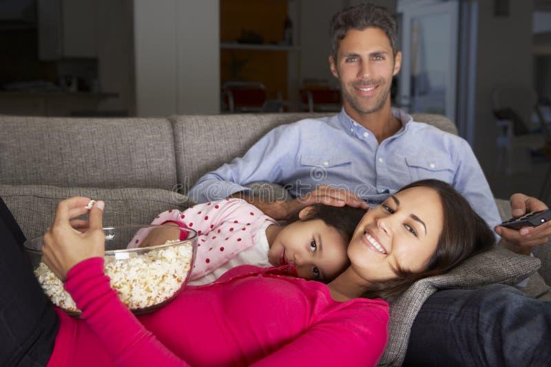 Famiglia ispana su Sofa Watching TV e sul popcorn di cibo immagini stock libere da diritti
