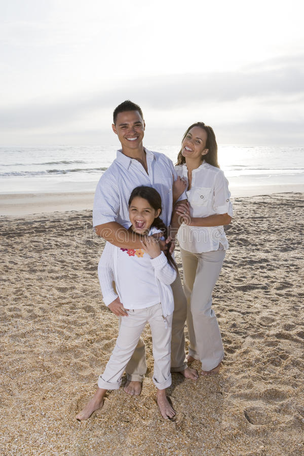 Famiglia ispanica con la bambina che si leva in piedi sulla spiaggia immagini stock