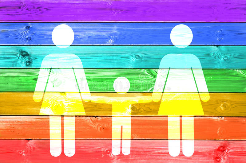 Famiglia lesbica con il segno bianco del bambino su un fondo di legno delle plance della bandiera gay dell'arcobaleno fotografia stock libera da diritti