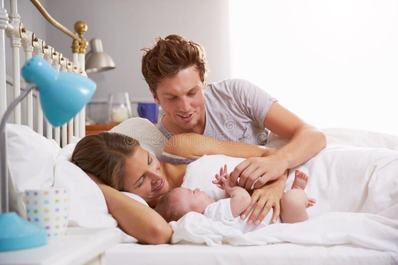 Famiglia a letto che tiene la figlia addormentata del neonato immagini stock
