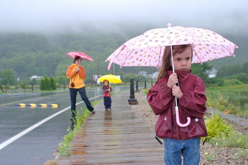 Famiglia sotto la pioggia immagine stock