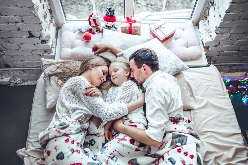 Famiglia, madre, padre felice e figlia riposanti sul letto bianco fotografia stock libera da diritti
