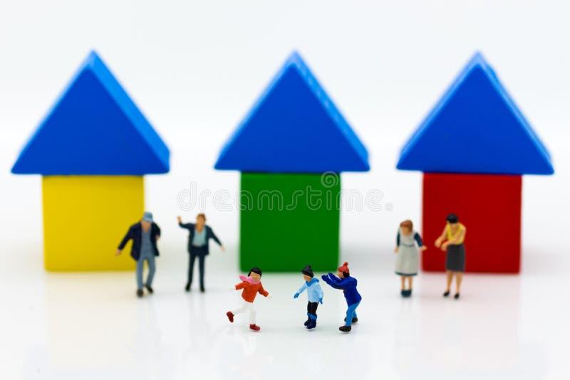 Famiglia miniatura: I bambini sono insieme gioco L'uso di immagine affinchè impara viva insieme alla società fotografie stock