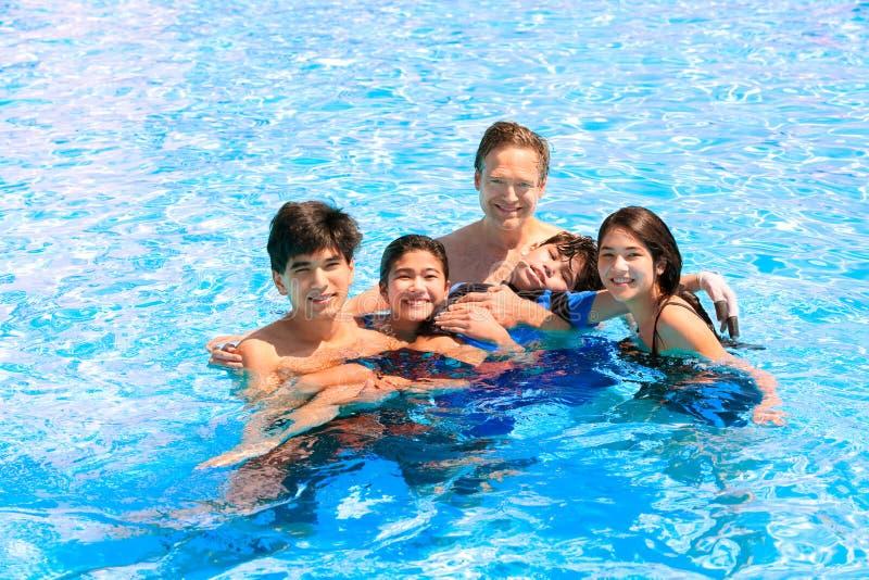 Famiglia multirazziale che nuota insieme nello stagno Più giovane disabile immagini stock libere da diritti