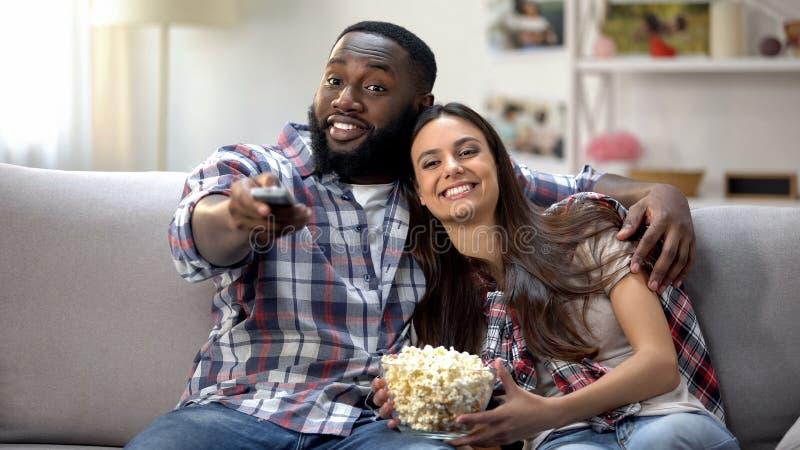 Famiglia multirazziale con i canali di commutazione del cereale di schiocco, programma di sorveglianza della TV a casa immagini stock