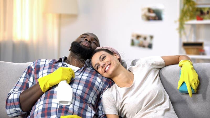 Famiglia multirazziale in guanti con lo spruzzo della pulitrice felice circa lavoro domestico fatto immagine stock