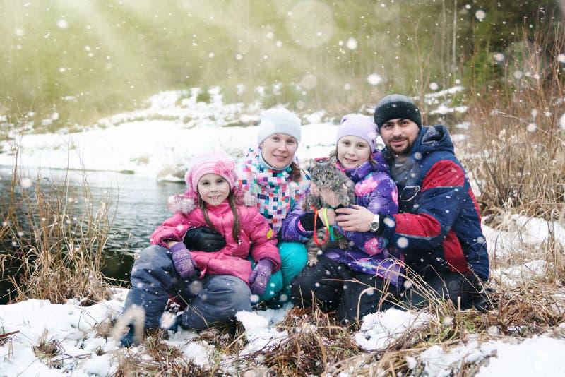 Famiglia in natura un giorno di inverno sotto precipitazioni nevose immagine stock