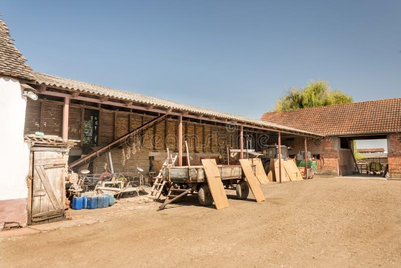 Famiglia nel villaggio con le stalle e trattori nell'iarda fotografia stock